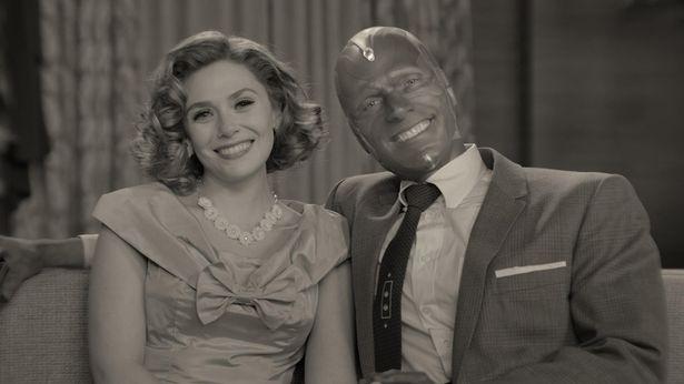 【写真を見る】ワンダ(エリザベス・オルセン)とヴィジョン(ポール・ベタニー)の笑顔の裏に不穏な空気を感じる