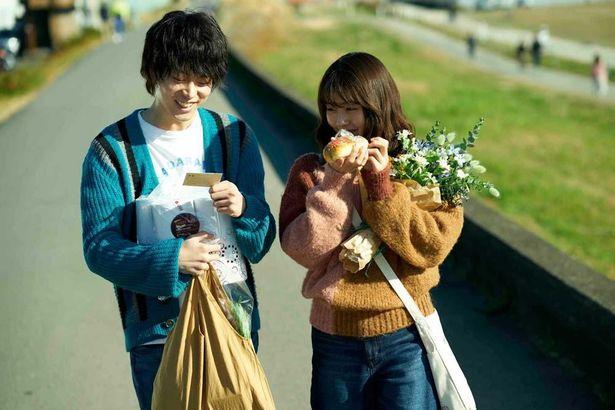 花束を持ちながら仲良く散歩する2人