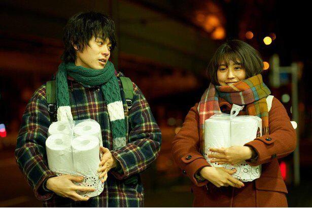 【写真を見る】『花束みたいな恋をした』より、トイレットペーパーの束を抱えながら並んで歩く菅田将暉と有村架純
