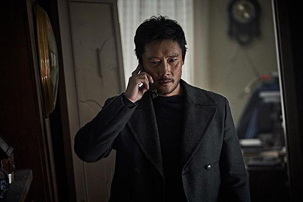 電話を片手に深刻な表情を浮かべるイ・ビョンホン演じる工作員リ・ジュンピョン