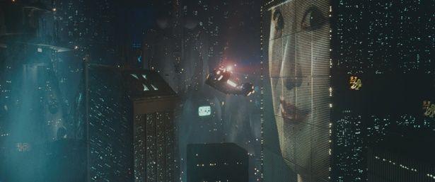 【写真を見る】ひしめき合う高速ビル、巨大な広告映像、空中を移動する車など、衝撃的な映像の連続に心を奪われた人は多い(『ブレードランナー ファイナル・カット』)