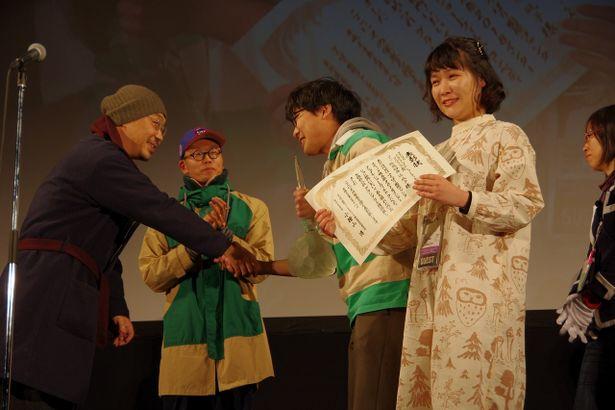 トロフィーを受け取る阪元裕吾監督と、うれし涙を見せた辻凪子監督
