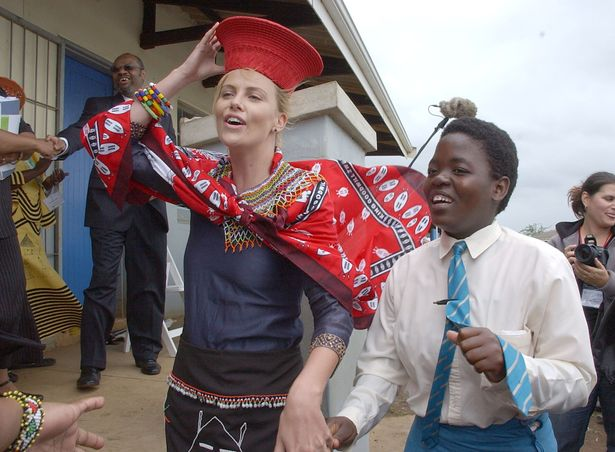 南アフリカの伝統的な衣装をまとって交流するシャーリーズ・セロン